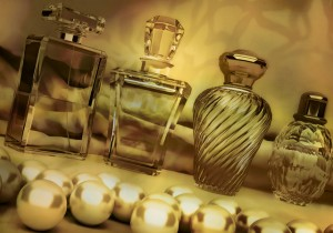 Pearls and different bottles of perfume on dark golden backgroun